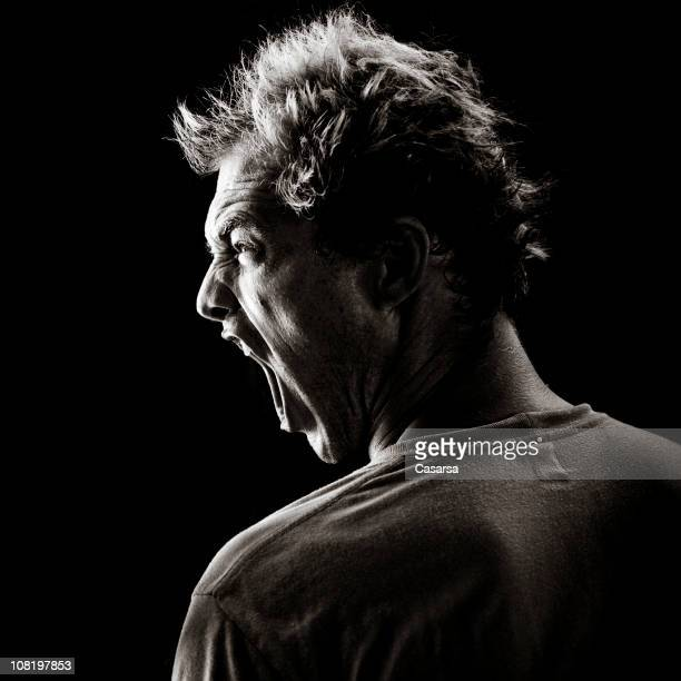 Young Man Yelling on Black Background