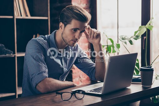 Young manager in checkered shirt reading information on the Internet on his computer : Stock Photo