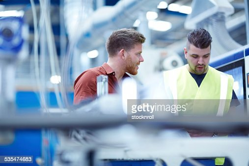Young manager with foreman on factory shopfloor