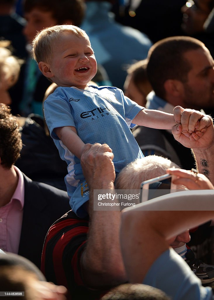 A young Manchester City fan enjoys the atmosphere as players parade the Barclays Premier League trophy in front of thousands of fans during their victory parade around the streets of Manchester on May 14, 2012 in Manchester, England.