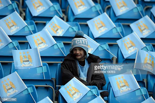 A young Manchester City supporter sits amongst the flags before the English Premier League football match between Manchester City and Manchester...