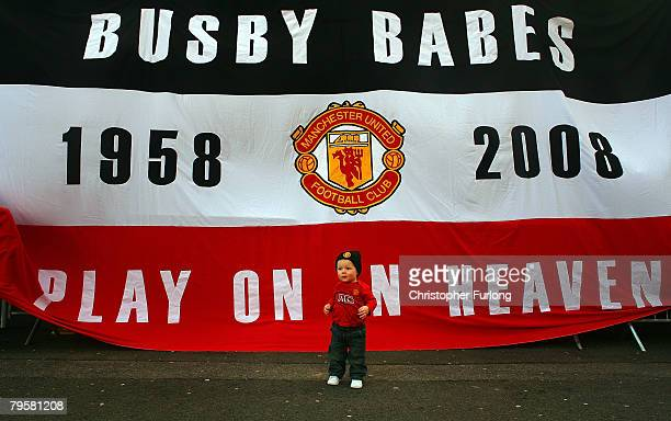 A young Manchester United fan poses in front of a banner for his mother to take a photo as fans take part in a minute's silence to mark 50 years...