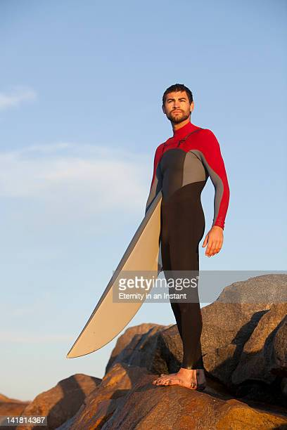 Young mand standing holding surfboard, portrait