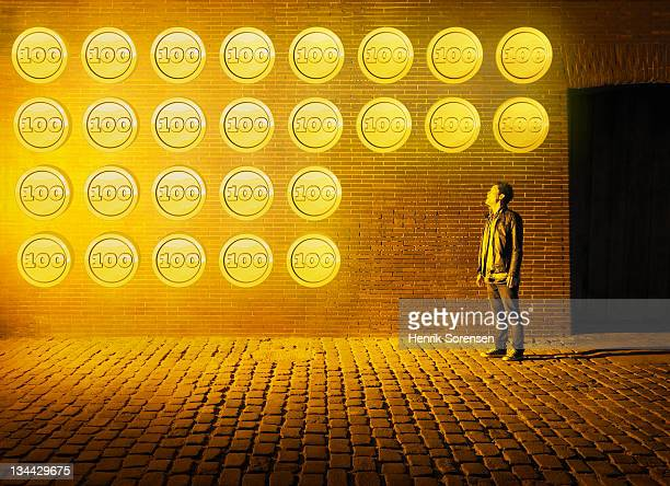 young manlooking at wall of coins
