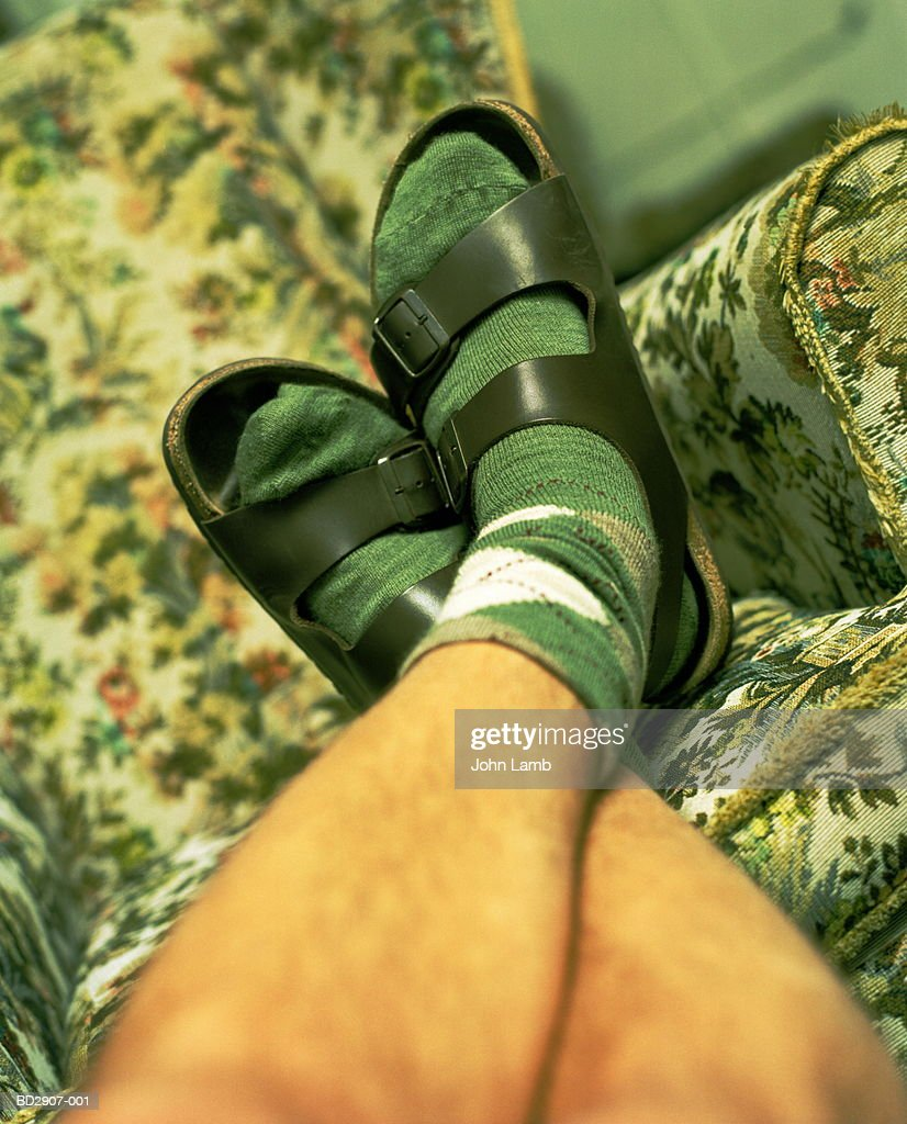 Young man's feet wearing socks and sandles, legs crossed at ankles : Foto de stock