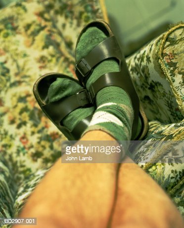 Young man's feet wearing socks and sandles, legs crossed at ankles : Stock Photo