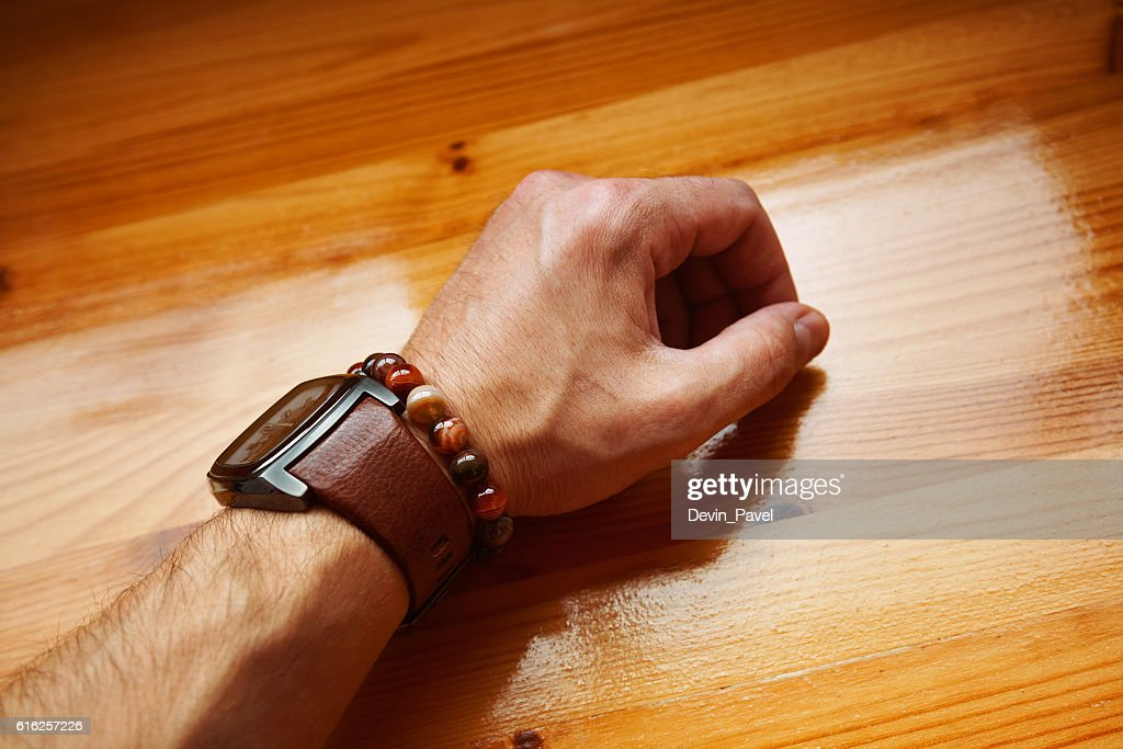 young man's hand with a watch and bracelet decoration : Foto de stock