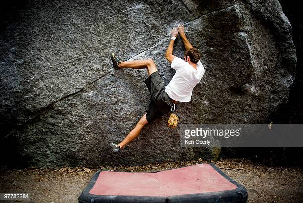 A young man's heal hooks a boulder located in Yosemite Valley, California.