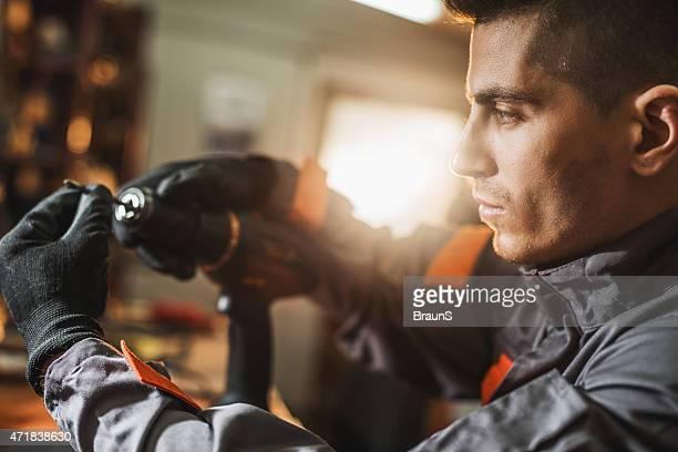 Junge Arbeiter anpassen Schraube auf eine elektrische Baumwolldrell.
