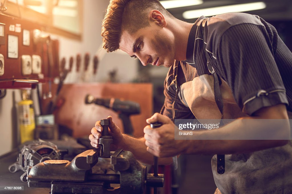Young manual worker working on a clamp at workshop.