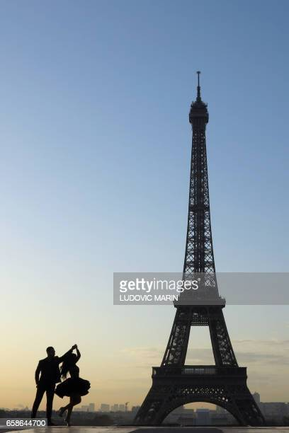 TOPSHOT A young married couple dances at sunrise on the Esplanade du Trocadero near the Eiffel tower on March 28 2017 in Paris / AFP PHOTO / Ludovic...