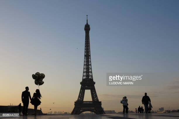 A young married couple is pictured at sunrise on the Esplanade du Trocadero near the Eiffel tower on March 28 2017 in Paris / AFP PHOTO / Ludovic...