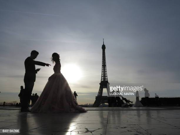 A young married couple of tourists make wedding pictures in front of the Eiffel tower at sunrise at the trocadero on February 25 in Paris / AFP /...