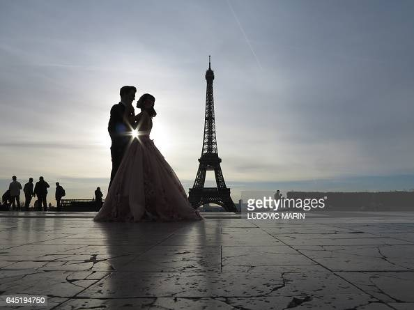 TOPSHOT A young married couple of tourists make wedding pictures in front of the Eiffel tower at sunrise at the trocadero on Febuary 25 in Paris /...