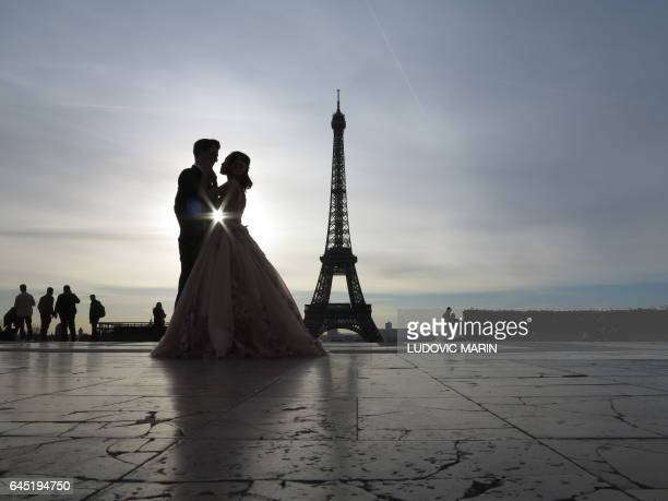 TOPSHOT A young married couple of tourists make wedding pictures in front of the Eiffel tower at sunrise at the trocadero on February 25 in Paris /...
