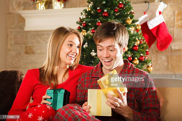 young married couple on Christmas morning opening gifts