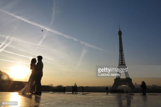 A young married couple poses in front of the Eiffel tower at sunrise on March 27 in Paris / AFP PHOTO / Ludovic MARIN