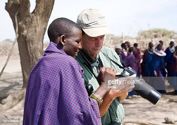 Young Masai warrior lokking at ta tourist's camera.
