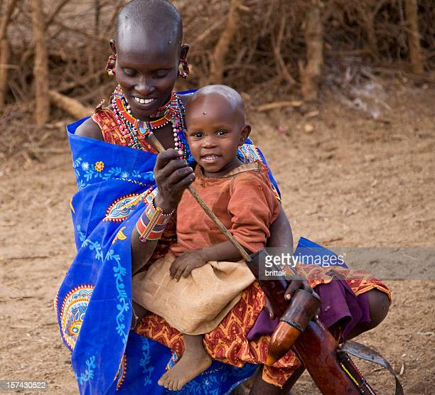 Young Masai woman with child cleaning calabash. Kenya.