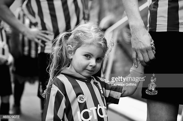 A young mascot holds the hand of a Bradford City player as they wait to take the field prior to the FA Cup Quarter Final betweeen Braford City and...