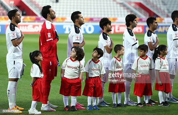 A young mascot looks at the Iraq players as they sing their nation al anthem ahead of the AFC U23 Championship semi final match between Japan and...