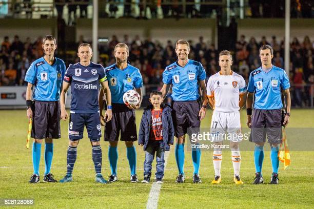 A young mascot tosses the coin with captains Matthew McKay of the Roar and Besart Berisha of the Victory before the FFA Cup round of 32 match between...