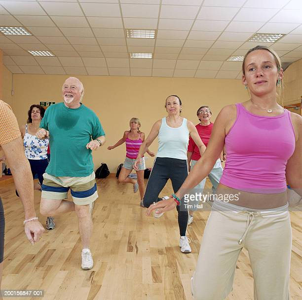 Young, mature and senior people exercising in aerobics class