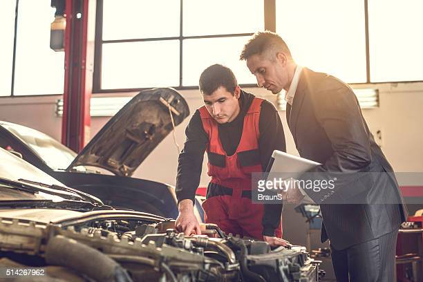 Young mechanic and manager examining a car engine.