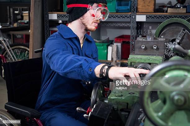 Jeune mécanicien/apprentis en fauteuil roulant en tournant Machine-outil de travail