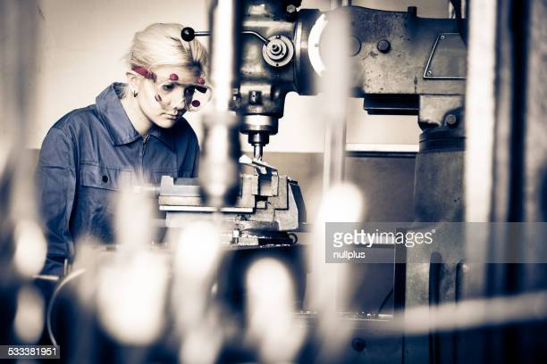 young mechanic / apprentice working on milling machine