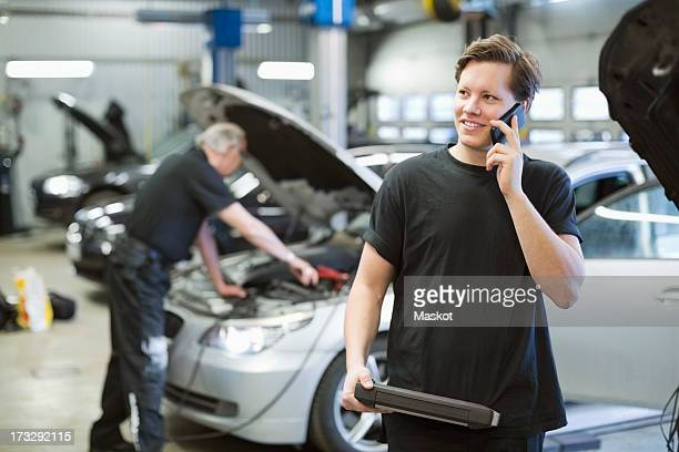 Young mechanic holding digital tablet using mobile phone with coworker working in background at workshop