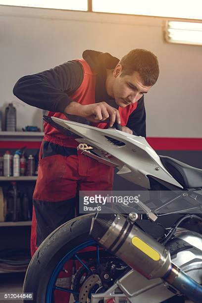 Young mechanic repairing a motorcycle in a workshop.