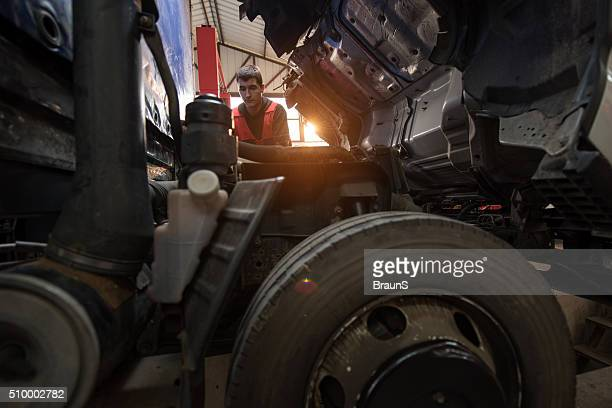 Joven mecánico arreglando un camión en un taller.