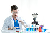 Young Medical Scientist Studying Reaction of Sample Chemical in Test Tube in White Laborator - Science and Technology Concept