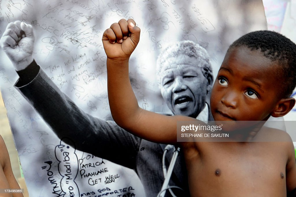 A young member of the Maitibolo Cultural Troupe poses on July 14, 2013 in front of a photograph of former South African President Nelson Mandela outside the Medi Clinic Heart Hospital in Pretoria. Graca Machel, the wife of Mandela, said she was less anxious about his condition on July 12, five weeks after he was admitted to hospital. After visiting Mandela late on July 11, President Jacob Zuma said he was 'responding to treatment.' Mandela was rushed to hospital on June 8 over a recurring lung infection.