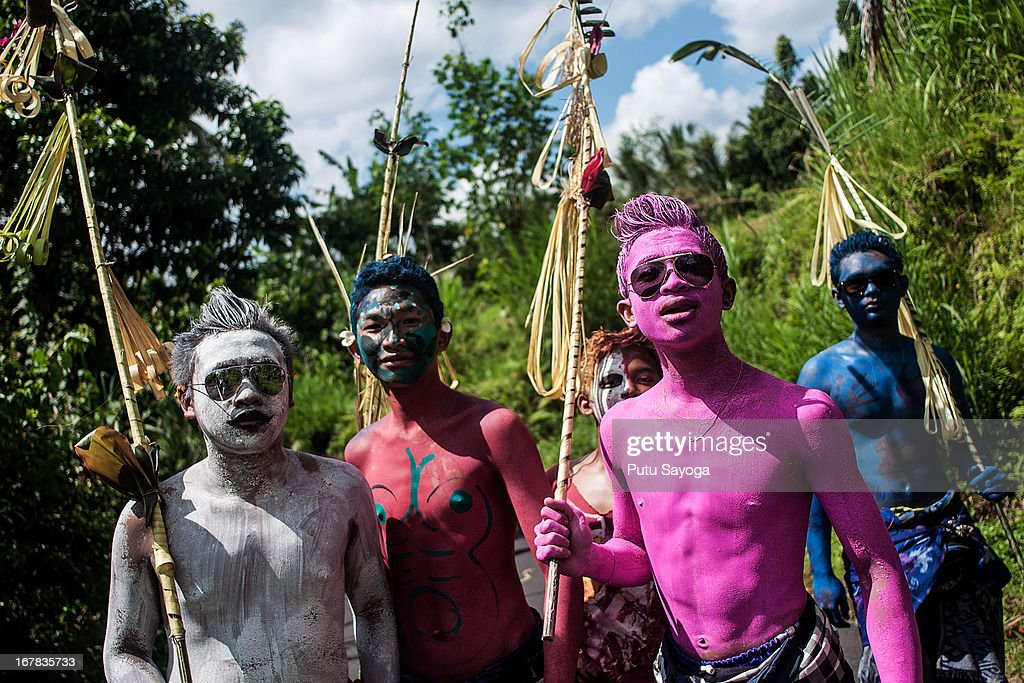 Young members of the village community walk around their village with painted bodies during the Grebeg Ritual on May 1, 2013 in Tegallalang, Bali, Indonesia. During the biannual ritual young members of the community parade through the village with painted faces and bodies to ward off evil spirits.