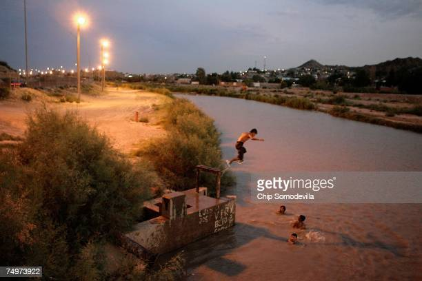 Young men and boys from Mexico jump into the Rio Grande from the United States side of the border with Mexico June 30 2007 in El Paso Texas The...