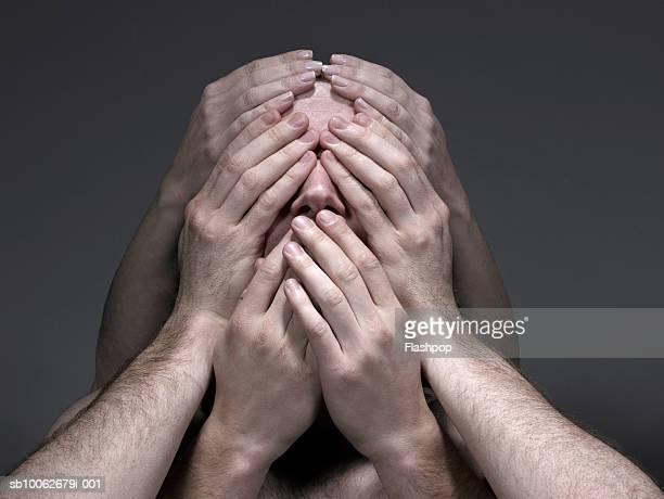Young men and woman covering face, close-up