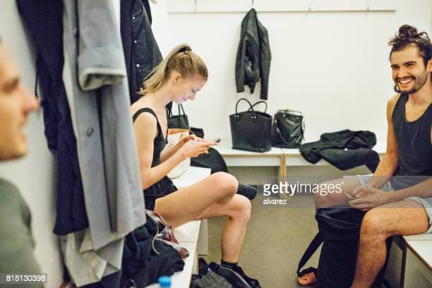 Young men and woman relaxing in locker room