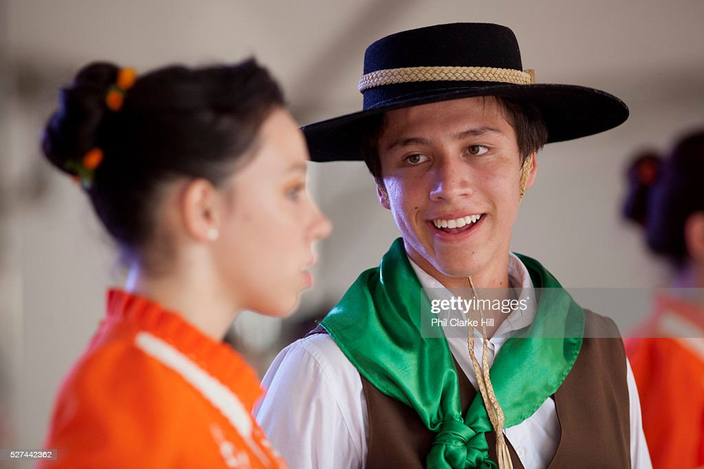 Young men and women boys and girls teenagers dancing on stage in couples wearing traditional Gaucho dancing costumes for a performance Reponte da...