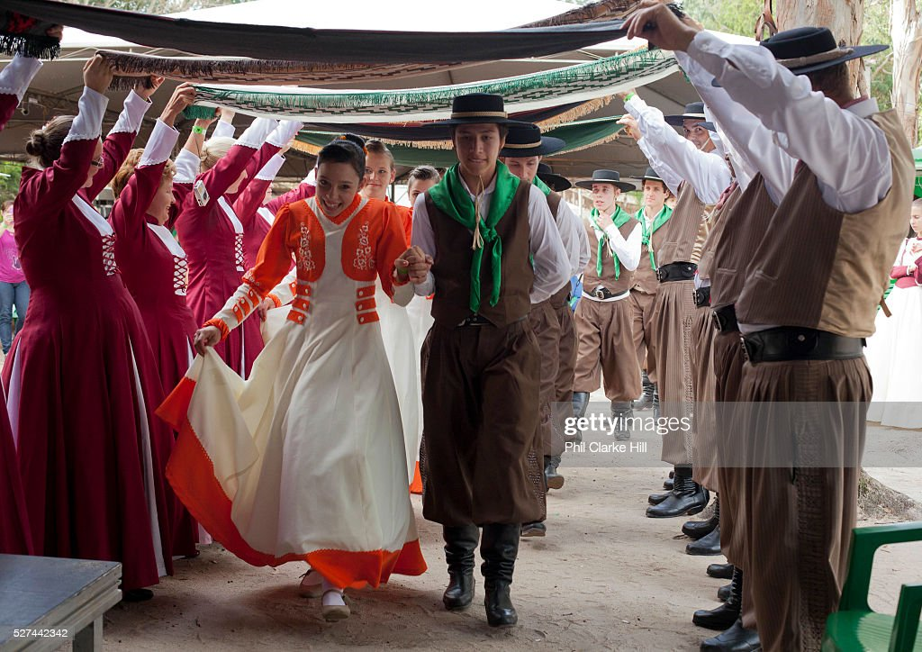 Young men and women boys and girls teenagers wearing traditional Gaucho dancing costumes for a performance Couple at front walking through a avenue...