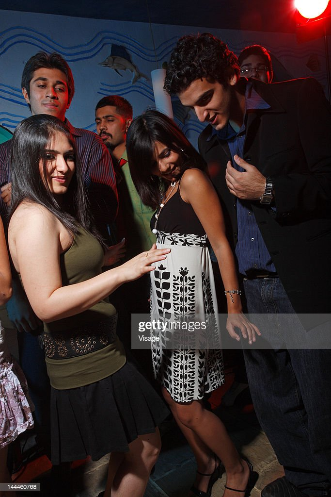 Young men and women dancing at a party : Stock Photo
