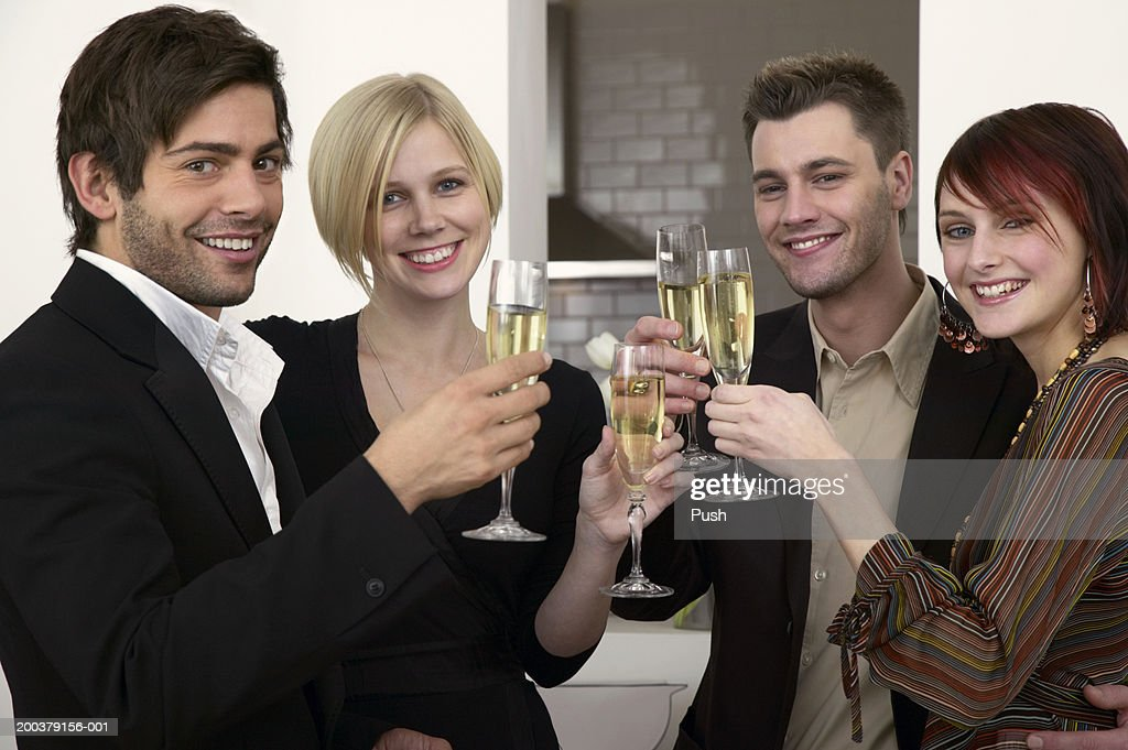Young men and women holding champagne flutes, smiling, portrait : Stock Photo