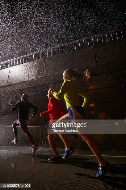 Young men and women jogging at night
