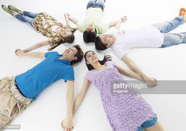 Young men and women lying on back