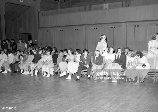 Young men and women sit awkwardly together on chairs beside the dance floor during a high school dance in the gymnasium at Monterey Union High School...