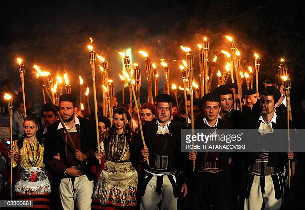 Young men and women with torches participate in the wedding procession a night before the ceremony 'Galicnik wedding' in the western Macedonian...