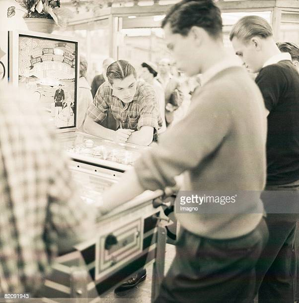 Young men at a pinball machine in an amusement arcade on Reeperbahn in Hamburg Photograph 1955/56 [Junge Mnner an einem Flipper in einer Spielhalle...
