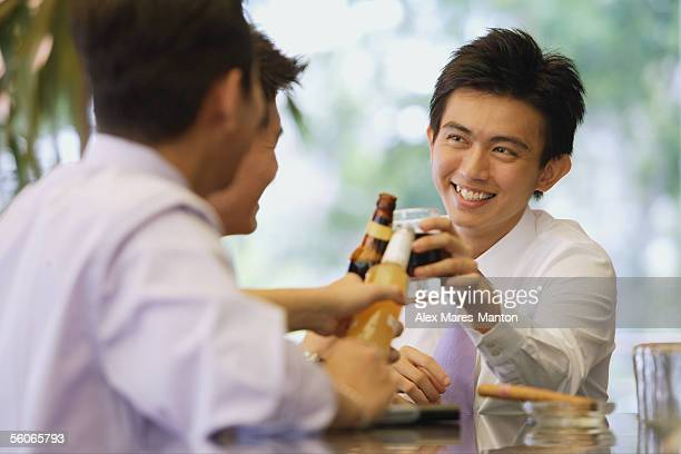 Young men at bar counter toasting with drinks