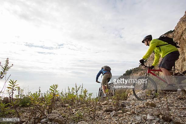 Hombres jóvenes en bicicleta de montaña vía, sobre el mar
